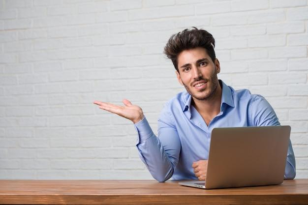 Junger geschäftsmann, der an einem laptop hält etwas mit den händen, ein produkt zeigend sitzt und arbeitet