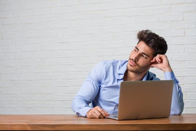 Junger geschäftsmann, der an einem laptop oben schaut sitzt und arbeitet