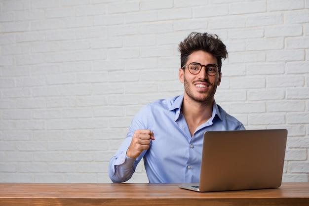 Junger geschäftsmann, der an einem laptop sehr glücklich und aufgeregt, arme anhebend sitzt und arbeitet