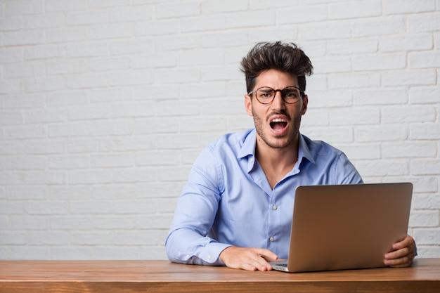 Junger geschäftsmann, der an einem laptop sehr verärgert und umgekippt sitzt und arbeitet