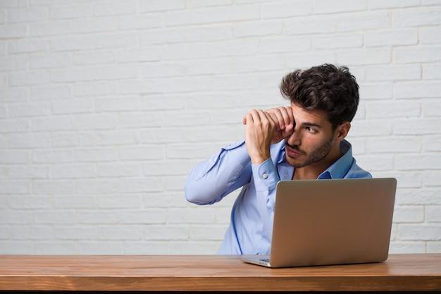 Junger geschäftsmann, der an einem laptop sitzt und arbeitet, der durch einen abstand schaut, sich versteckt und schielen