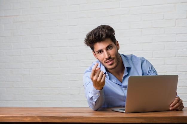 Junger geschäftsmann, der an einem laptop sitzt und arbeitet, der einlädt zu kommen