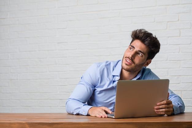 Junger geschäftsmann, der an einem laptop sitzt und arbeitet, der oben schaut, an etwas spaß denkt und eine idee, ein konzept der fantasie, glücklich und aufgeregt hat