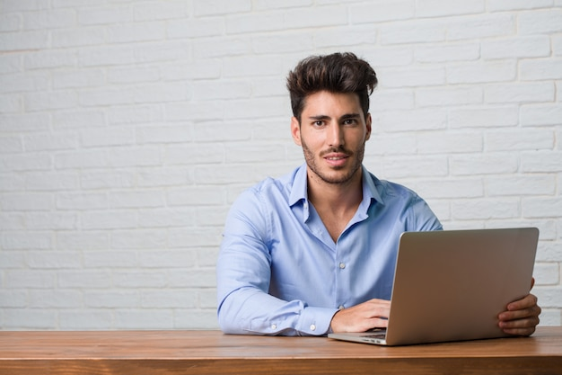 Junger geschäftsmann, der an einem laptop sitzt und arbeitet, der seine arme kreuzt, lächelt und glücklich und überzeugt und freundlich ist