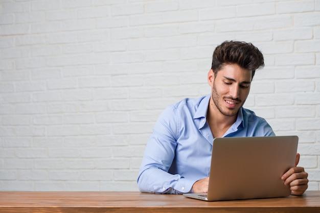 Junger geschäftsmann, der an einem laptop sitzt und arbeitet, der spaß lacht und hat