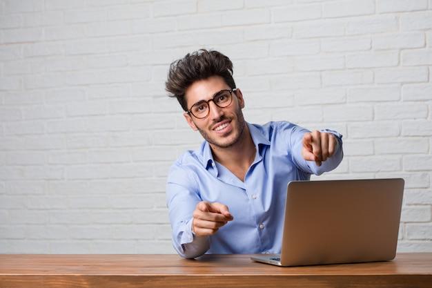 Junger geschäftsmann, der an einem laptop sitzt und arbeitet