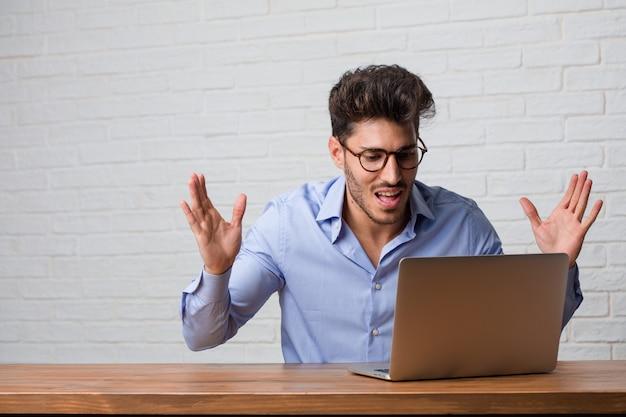 Junger geschäftsmann, der an einem schreienden laptop glücklich sitzt und arbeitet