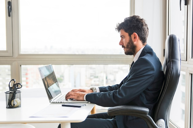 Junger geschäftsmann, der an laptop am arbeitsplatz arbeitet
