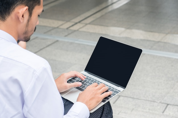 Junger geschäftsmann, der an laptop arbeitet