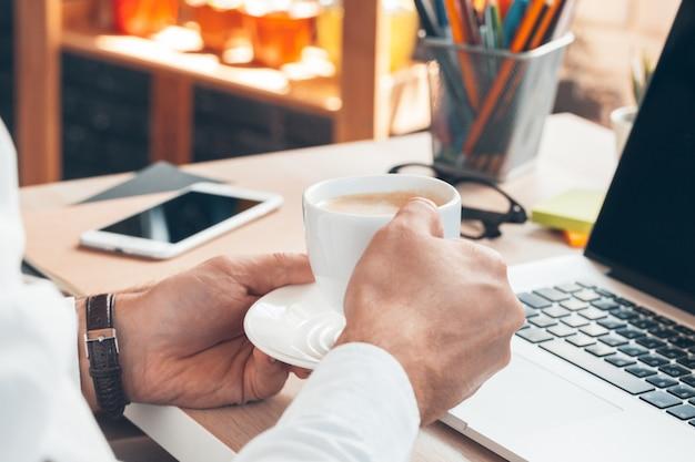 Junger geschäftsmann, der an laptop-computer mit heißem kaffee in der hand arbeitet.