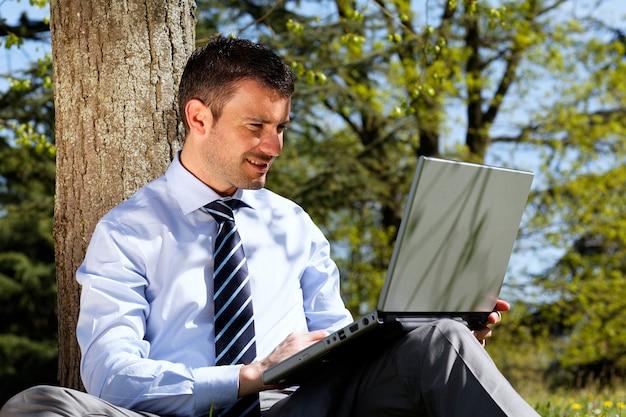 Junger geschäftsmann, der an laptop in einem park arbeitet