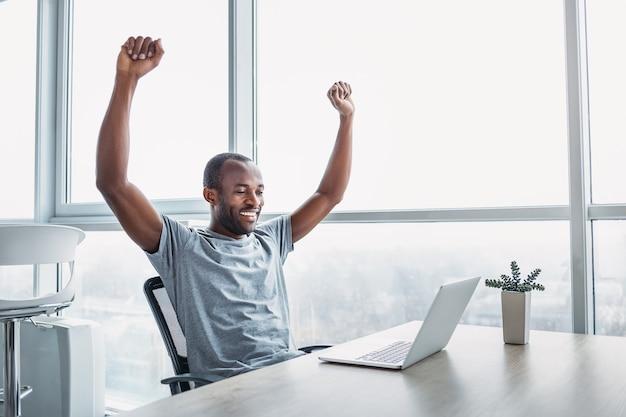 Junger geschäftsmann, der an seinem laptop in einem geräumigen hellen büro arbeitet