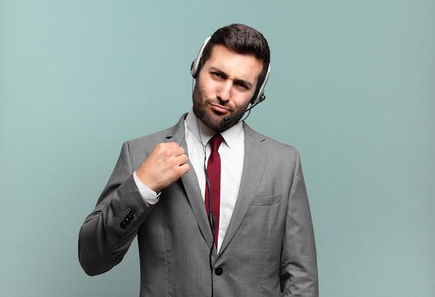 Junger geschäftsmann, der arrogant, erfolgreich, positiv und stolz aussieht und auf selbst-telemarketing-konzept zeigt