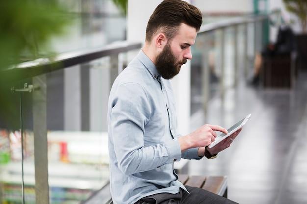 Junger geschäftsmann, der auf bank im korridor unter verwendung der digitalen tablette sitzt