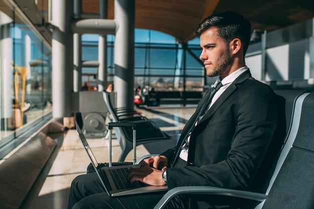 Junger geschäftsmann, der auf dem computer mit dem koffer am flughafen wartet auf den flug sitzt