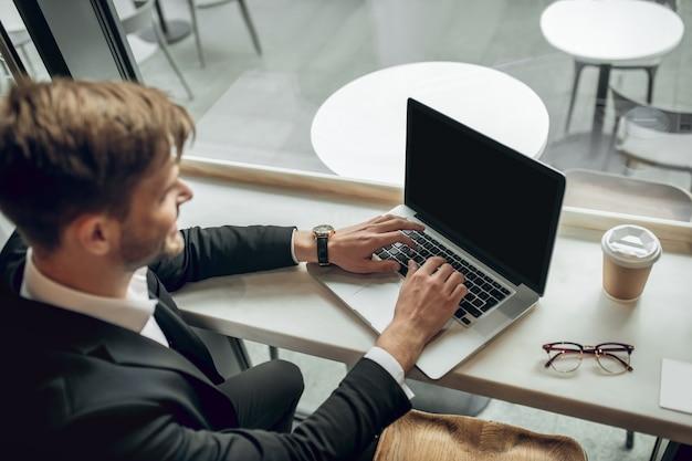 Junger geschäftsmann, der auf dem laptop in einem café arbeitet und beteiligt schaut