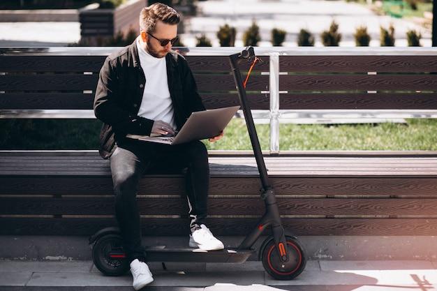 Junger geschäftsmann, der auf der bank sitzt und am computer arbeitet