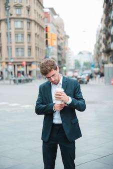 Junger geschäftsmann, der auf der straße hält die kaffeetasse in der hand justiert seinen ärmel steht