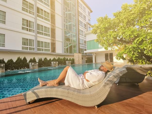 Junger geschäftsmann, der auf einem deckchair durch einen swimmingpool sich entspannt