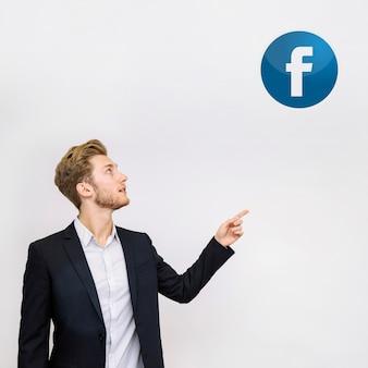 Junger geschäftsmann, der auf facebook-ikone auf wand zeigt