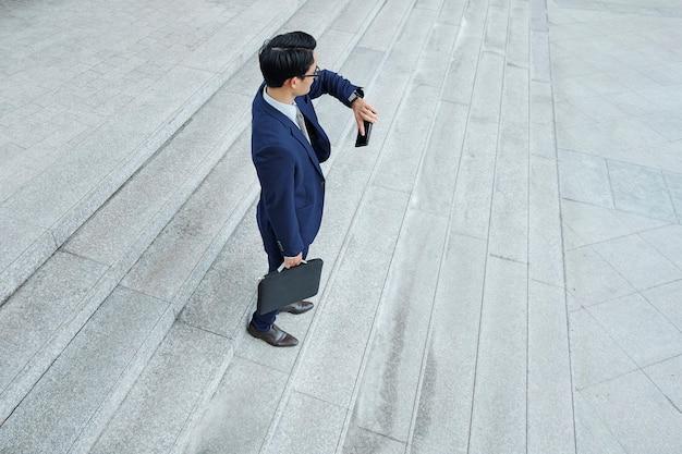 Junger geschäftsmann, der auf kollegen draußen wartet und zeit auf smartwatch prüft