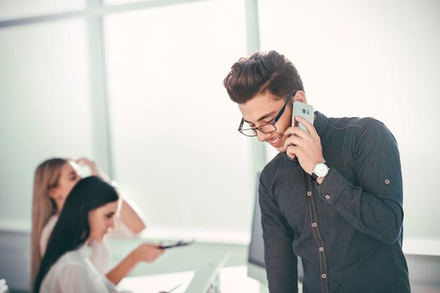 Junger geschäftsmann, der auf seinem smartphone im büro spricht. foto mit textfreiraum