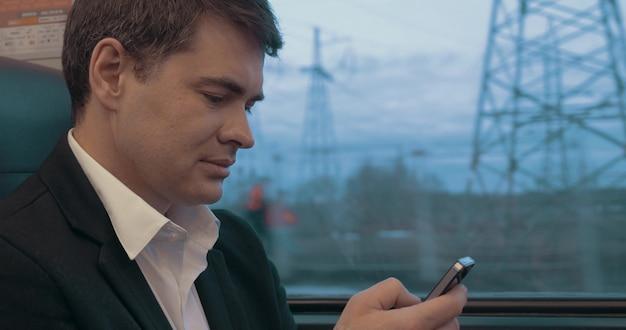 Junger geschäftsmann, der auf smartphone beim reisen mit dem zug eine sms sendet