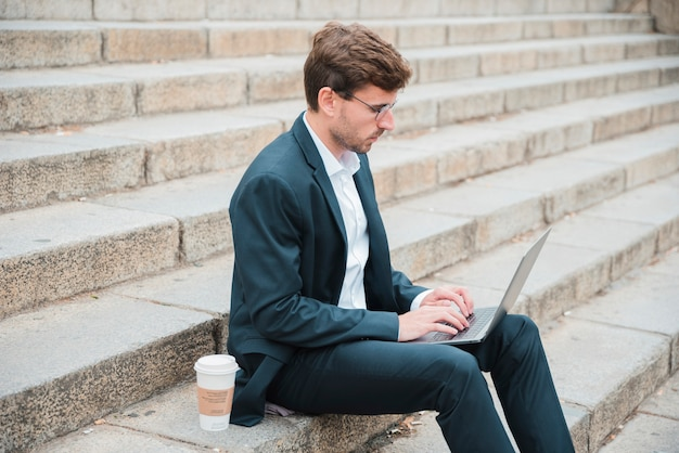 Junger geschäftsmann, der auf treppenhaus mit wegwerfkaffeetasse unter verwendung des laptops sitzt