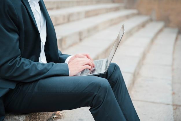 Junger geschäftsmann, der auf treppenhaus unter verwendung des laptops sitzt