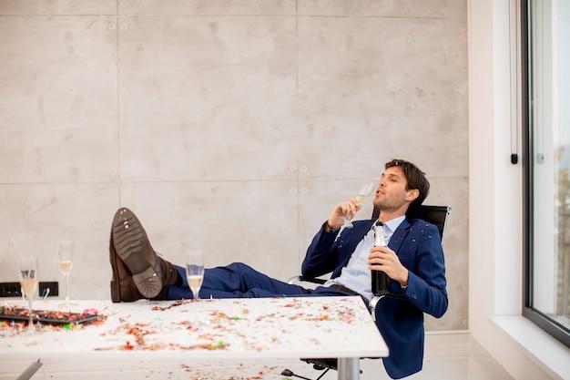 Junger geschäftsmann, der champagner im büro nach weihnachtsfeier trinkt