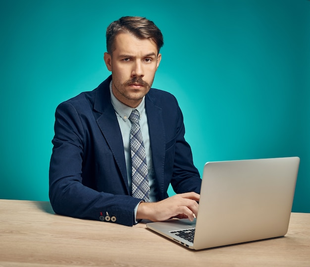 Junger geschäftsmann, der computer im büro benutzt