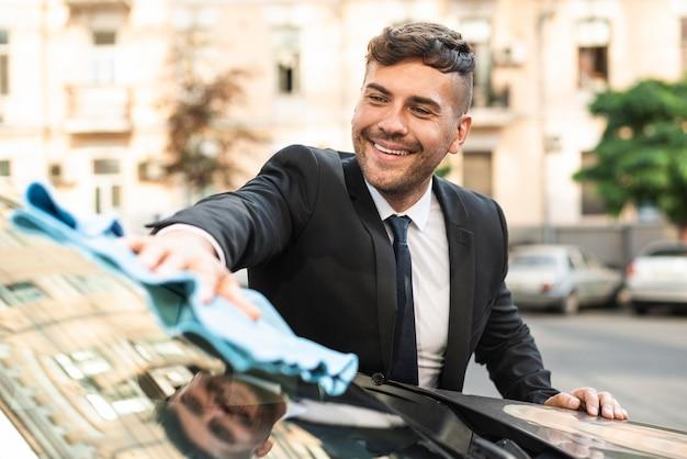 Junger geschäftsmann, der das auto reinigt
