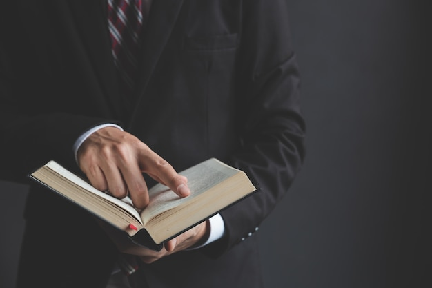 Junger geschäftsmann, der die heilige bibel liest