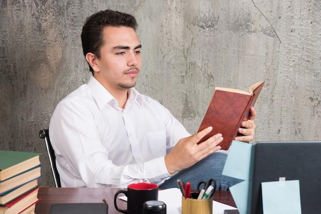Junger geschäftsmann, der ein buch am schreibtisch liest.