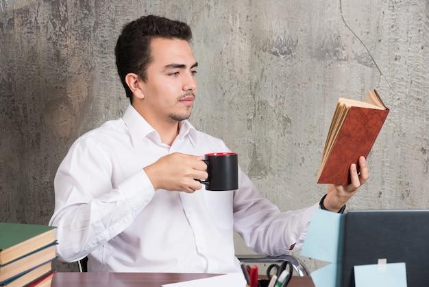 Junger geschäftsmann, der ein buch liest und seinen tee am schreibtisch trinkt.