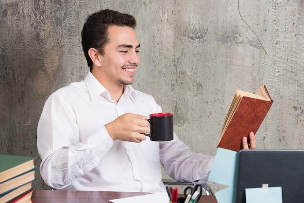 Junger geschäftsmann, der ein buch liest, während er seinen tee am schreibtisch trinkt.