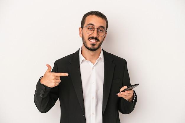 Junger geschäftsmann, der ein mobiltelefon isoliert auf weißem hintergrund hält, der mit der hand auf einen hemdkopierraum zeigt, stolz und selbstbewusst