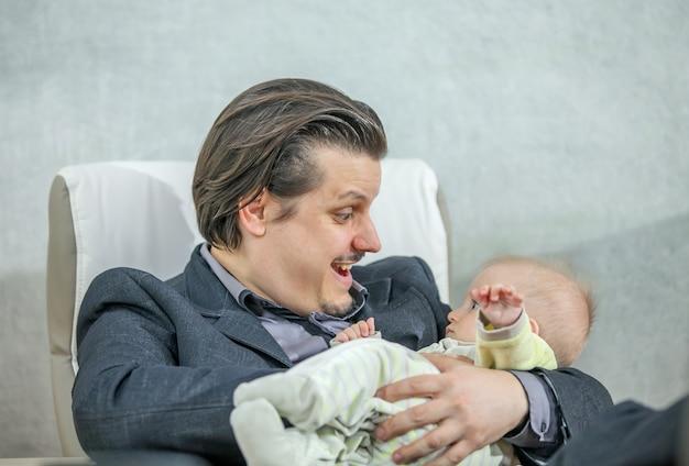 Junger geschäftsmann, der ein niedliches baby hält