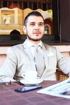 Junger geschäftsmann, der eine tasse kaffee während des sitzens an einem kaffeetourterrassentisch trinkt
