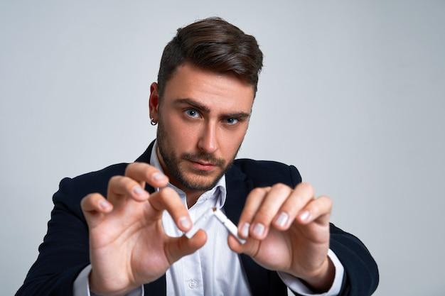 Junger geschäftsmann, der eine zigarette bricht