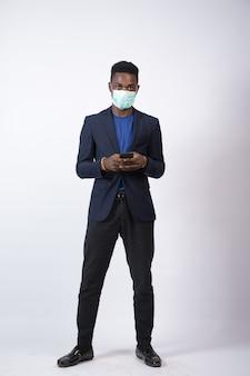Junger geschäftsmann, der einen anzug und eine gesichtsmaske mit seinem telefon trägt
