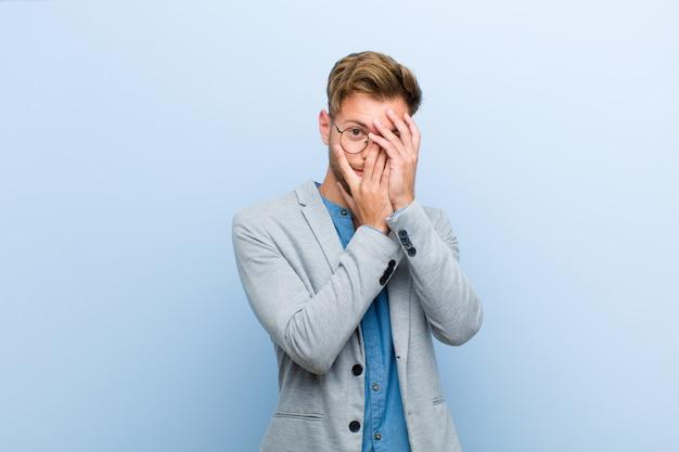 Junger geschäftsmann, der erschrocken oder verlegen sich fühlt, mit den augen späht oder ausspioniert, die mit den händen gegen blaue wand halb bedeckt sind