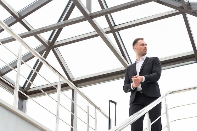 Junger geschäftsmann, der formellen anzug trägt, der auf einer treppe im modernen gebäude mit koffer steht
