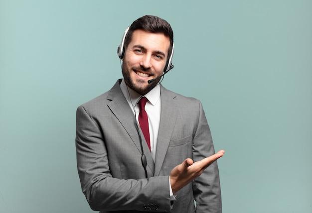 Junger geschäftsmann, der fröhlich lächelt, sich glücklich fühlt und ein konzept im kopienraum mit handflächen-telemarketing-konzept zeigt