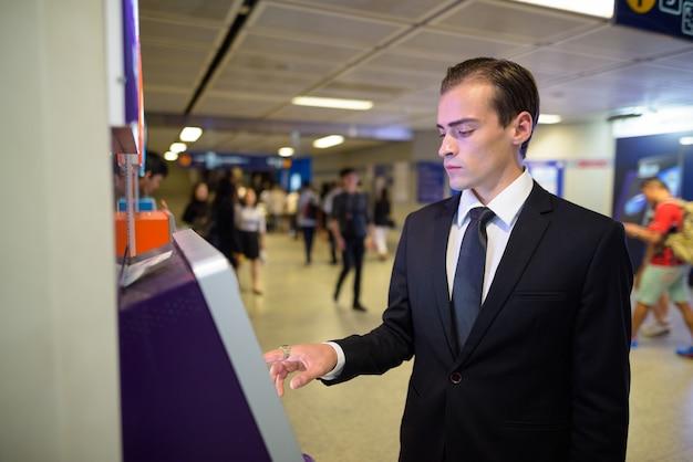 Junger geschäftsmann, der geldautomaten am bahnhof benutzt