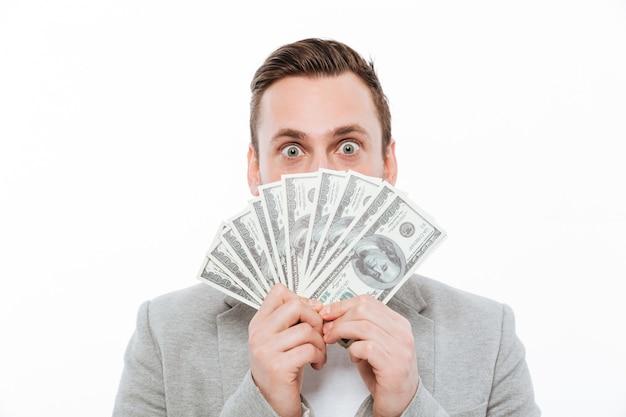 Junger geschäftsmann, der geldbedeckungsgesicht hält.