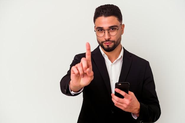 Junger geschäftsmann der gemischten rasse, der einen mobiltelefonmann lokalisiert auf weißer wand hält, die nummer eins mit finger zeigt.