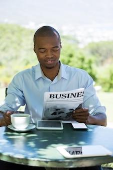 Junger geschäftsmann, der geschäftszeitung am restaurant liest
