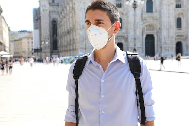 Junger geschäftsmann, der gesichtsmaske schützt, die für die ausbreitung des coronavirus in mailand, italien schützt