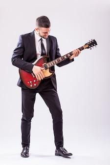 Junger geschäftsmann, der gitarre lokalisiert auf weißer wand spielt